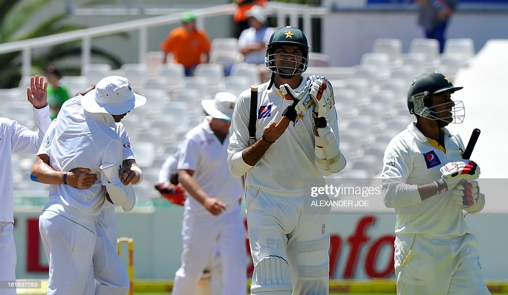 Pakistan cricketer Muhammad Irfan and Pakistan cricketer Tanvir Ahmed walk back to the pavillion after being all out for 182 on day four of the second test between South Africa and Pakistan in Cape Town at Newlands on February 17, 2013.