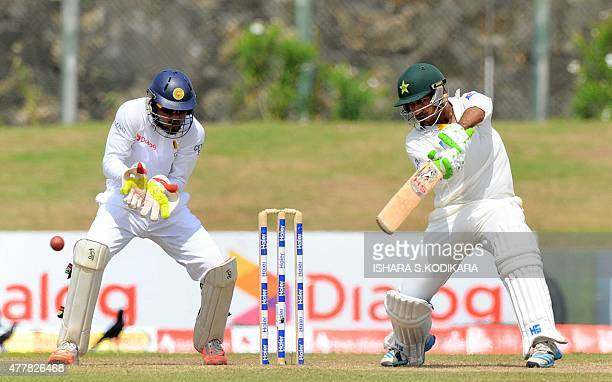 Pakistan cricketer Sarfraz Ahmed plays a shot as Sri Lankan wicketkeeper Dinesh Chandimal looks on during the fourth day of the opening Test match...