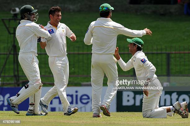 Pakistan cricketer Yasir Shah celebrates with teammates after he dismissed unseen Sri Lankan batsman Upul Tharanga during the opening day of the...