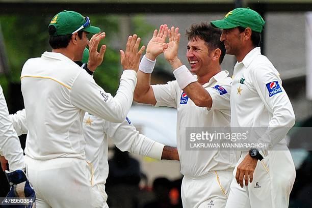 Pakistan cricketer Yasir Shah celebrates with teammates after he dismissed Sri Lankan batsman Kumar Sangakkara during the final day of the second...