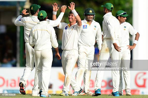 Pakistan cricketer Yasir Shah celebrates with teammates the dismissal of Sri Lankan cricketer Tharindu Kaushal during the second day of the second...