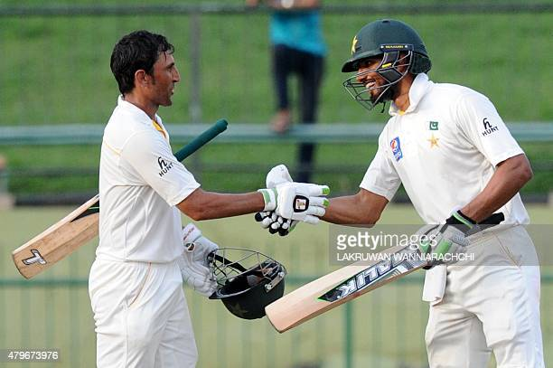 Pakistan cricketer Younis Khan is congratulated by teammate Shan Masood after he scored a century during the fourth day of the third and final Test...