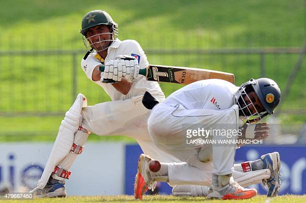 Pakistan cricketer Younis Khan plays a shot as Sri Lankan cricketer Lahiru Thirimanne reacts during the fourth day of the third and final Test match...