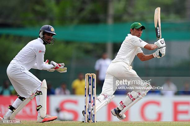 Pakistan cricketer Younis Khan plays a shot as Sri Lankan wicketkeeper Dinesh Chandimal looks on during the third day of the second Test cricket...
