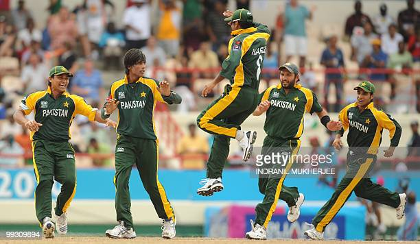 Pakistan cricketers run in to congratulate teammate Mohammad Aamer as they celebrate the wicket of Australian cricketer Shane Watson during the ICC...
