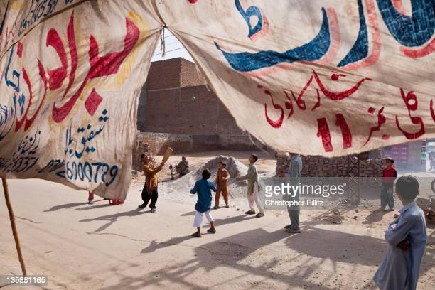 Pakistan - Faisalabad - Playing cricket in street.