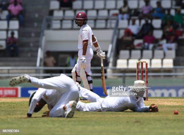 Pakistan fielders Younis Khan and Babar Azam try to stop a hook shot from West Indies batsman Vishaul Singh on the fifth day of play of the final...