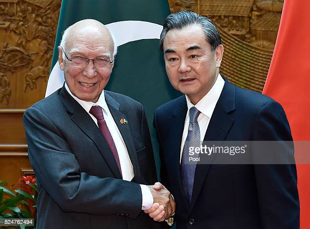 Pakistan Foreign Affairs Adviser Sartaj Aziz shakes hands with Chinese Foreign Minister Wang Yi before a meeting at the Ministry of Foreign Affairs...
