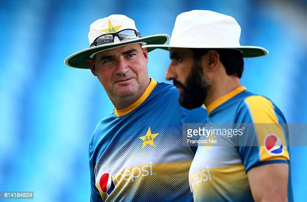 Pakistan Head Coach Mickey Arthur speaks to MisbahulHaq of Pakistan during a nets session at Dubai International Cricket Ground on October 12 2016 in...