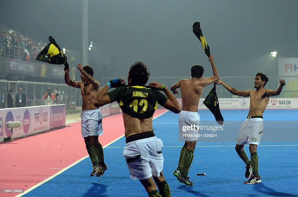 Pakistan hockey captain Imran Muhammad and teammates take their jerseys off as they celebrate their victory over India with teammates during their...