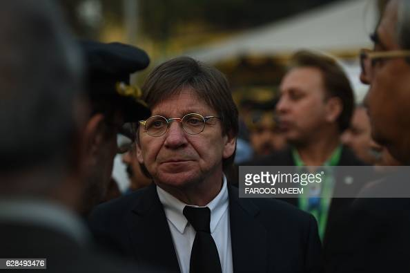 Pakistan International Airlines Chief Executive Officer Bernd Hildenbrand is surrounded by officials after inabsentia funeral prayers for the victims...