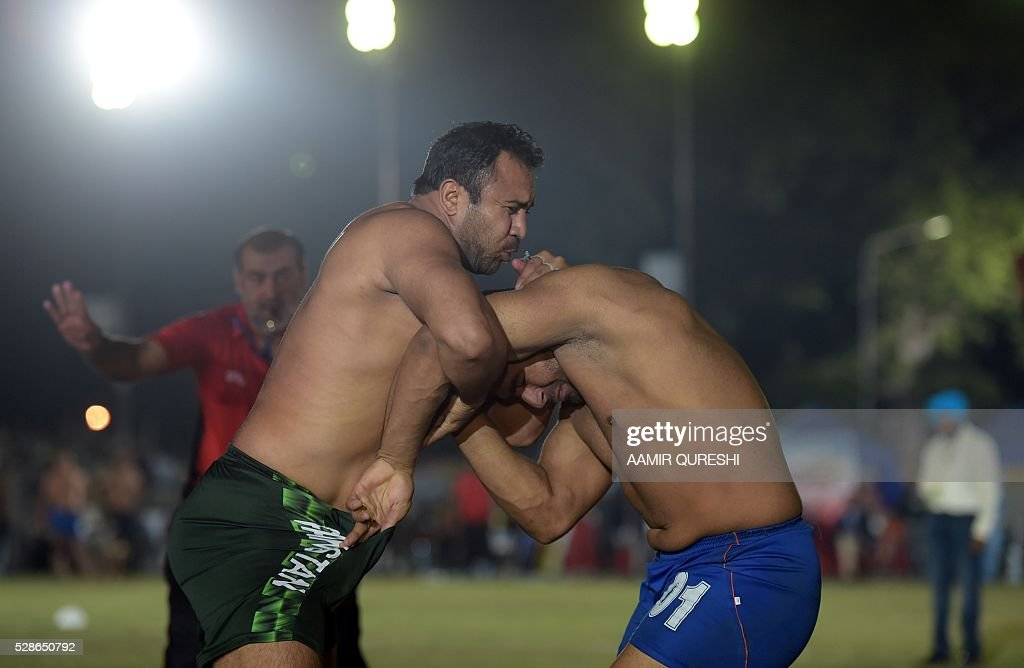 A Pakistan kabaddi player (L) is tackled by an Indian opponent during their final match of the 3rd Asian Kabaddi Circle Style Championship 2016 in Wah some 45 kilometers from Islamabad on May 6, 2016. Pakistan won the final match against India, scoring 50-31. / AFP / AAMIR
