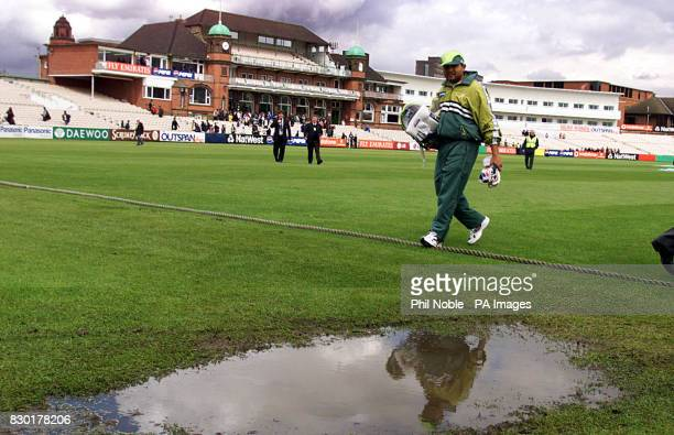 Pakistan leg spinner Mushtaq Ahmed walks passed a puddle as he walks to the nets after the World Cup warm up game against Lancashire at Old Trafford...