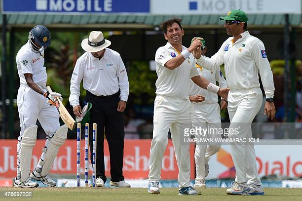 Pakistan legspinner Yasir Shah celebrates with teammates the dismissal of Sri Lankan cricketer Dushmantha Chameera during the third day of the second...