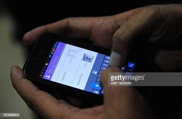 A Pakistan man tries to connect to chat with his friend on his mobile in the port city of Karachi on October 3 2013 Pakistan's southern Sindh...