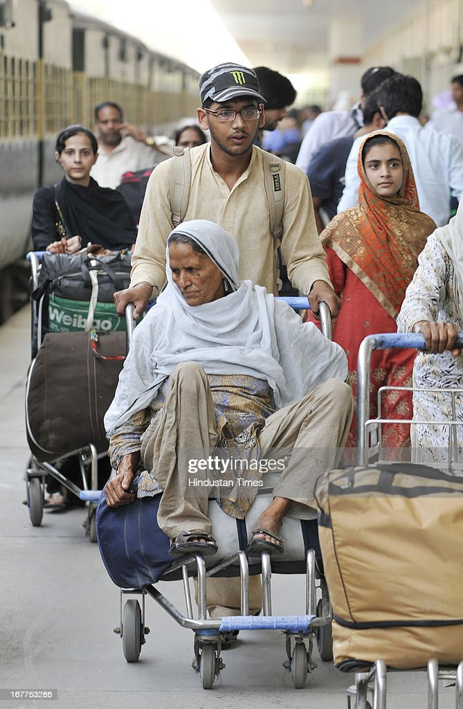 Pakistan national Mohd. Asim pushing his old family member on luggage trolley after reaching in India through Pakistan-India bound Samjhauta Express train at Attari Railway Station, at India-Pakistan Attari border on April 29, 2013 near Amritsar, India. Security has been enhanced at border in of wake deadly attack on Indian prisoner Sarabjit Singh in Pakistan Jail.