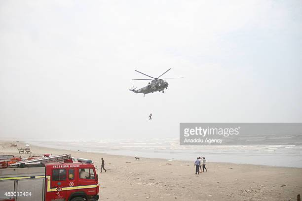 Pakistan Navy rescuer hanging from the crane line of a Sea King helicopter recovers the body of a drowning victim over Clifton beach in Karachi...