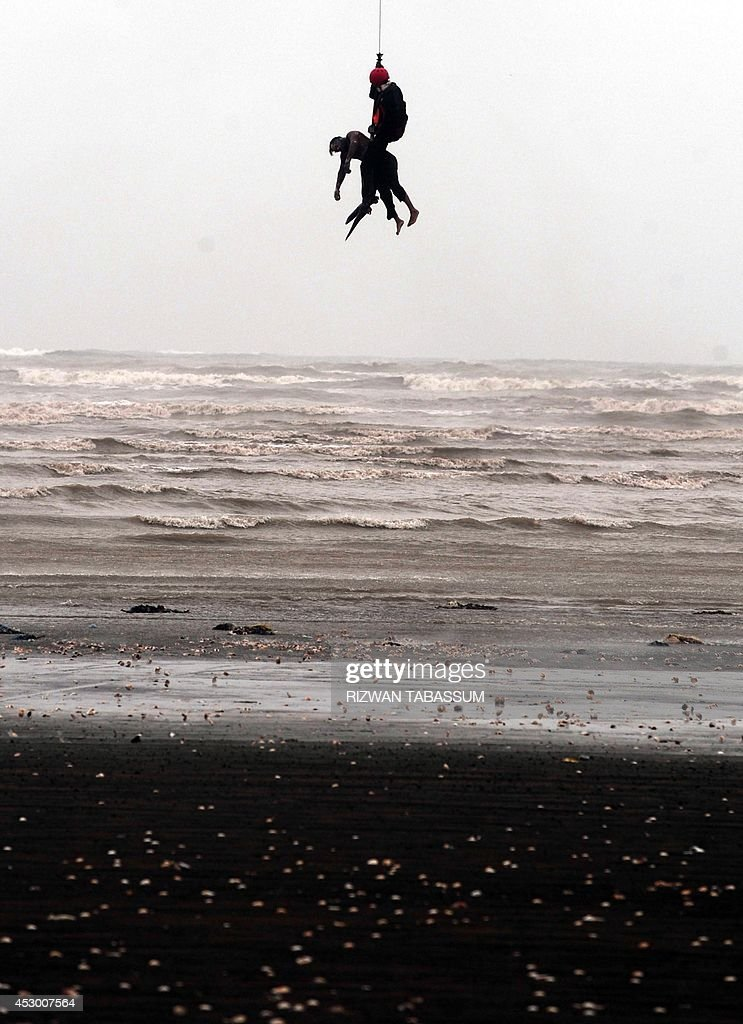 A Pakistan Navy rescuer hanging from the winch line of a Sea King helicopter recovers the body of a drowning victim over Clifton beach in Karachi on...