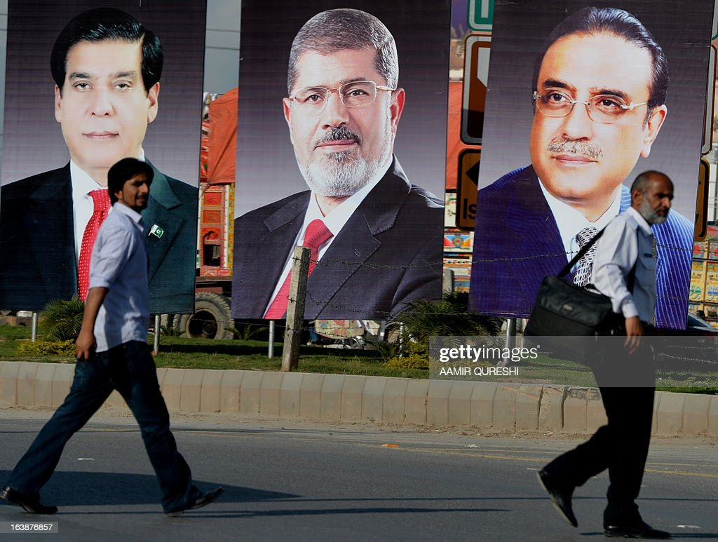 Pakistan pedestrians walk past billboards featuring photographs of Egyptian President Mohamed Morsi, (C), Pakistani President Asif Ali Zardari (R) and Prime Minister Raja Pervez Ashraf along a street in Islamabad on March 17, 2013. Morsi will visit Pakistan this week on a one-day state visit, Pakistan's Foreign Ministry said. Morsi is due in the country on March 18 by invitation of President Asif Ali Zardari and will bring with him 'a high-powered delegation', according to a ministry spokesman.