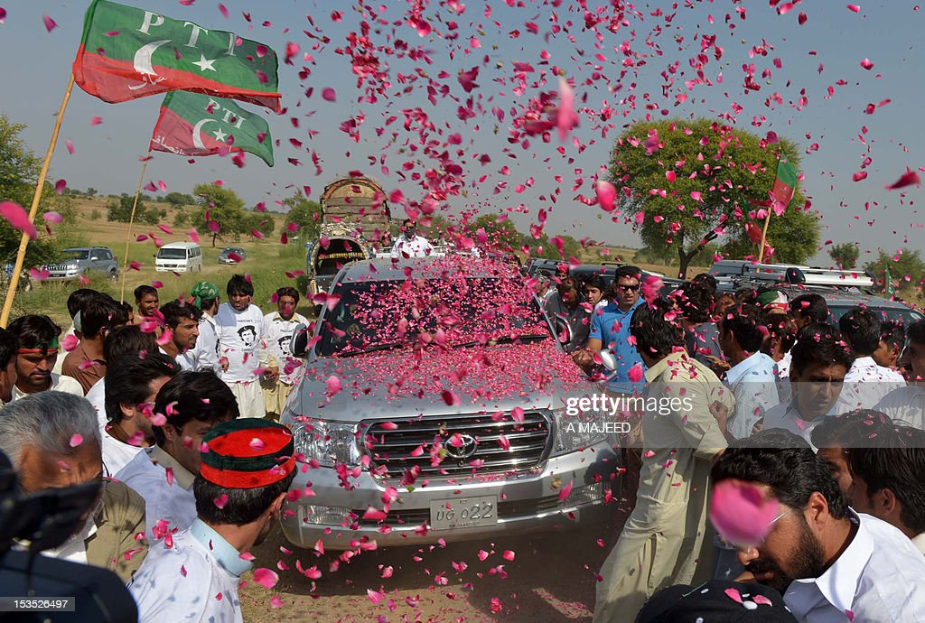 Pakistan people welcome the convoy of cricket star turned politician Imran Khan on his rally towards the tribal areas, in Mianwali on October 6, 2012. Pakistan cricket star turned politician Imran Khan led Western peace activists and local loyalists on a highly publicised rally to Pakistan's tribal belt Saturday in protest against US drone strikes. AFP PHOTO/A MAJEED