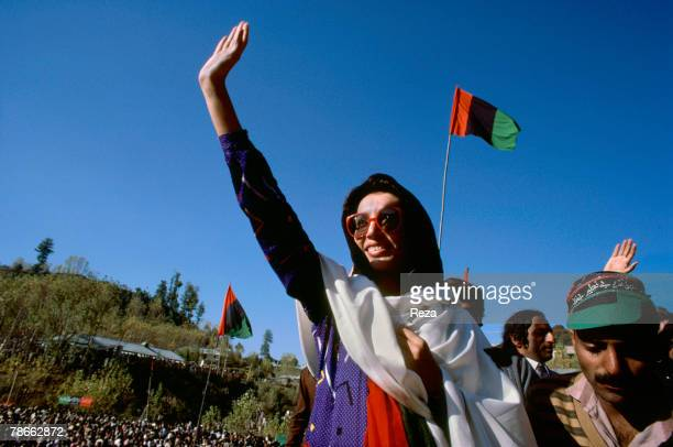 Pakistan People's Party candidate Benazir Bhutto waves at supporters displaying the red black and green PPP flag as she travels during the election...