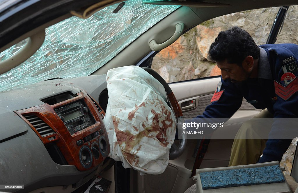 A Pakistan policeman inspects a damaged car after the local political leader's convoy was attacked in Pakistan's northwest city of Charsadda on January 12, 2013. Several people were injured in the roadside bomb blast which targeted the local political leader of the secular Awami National party Bashir Omarzai who survived the attack.