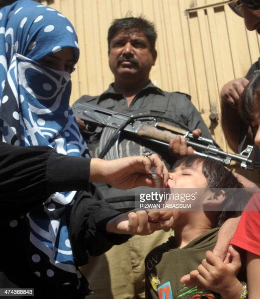 A Pakistan policeman stands guard as a member of a polio vaccination team administers drops to a child during a doortodoor vaccination campaign in...