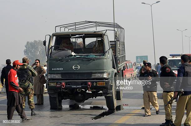 Pakistan policemen and army soldiers stand next to a damaged army vehicle after an Improvised Explosive Device blast in Peshawar on January 3 2016 A...