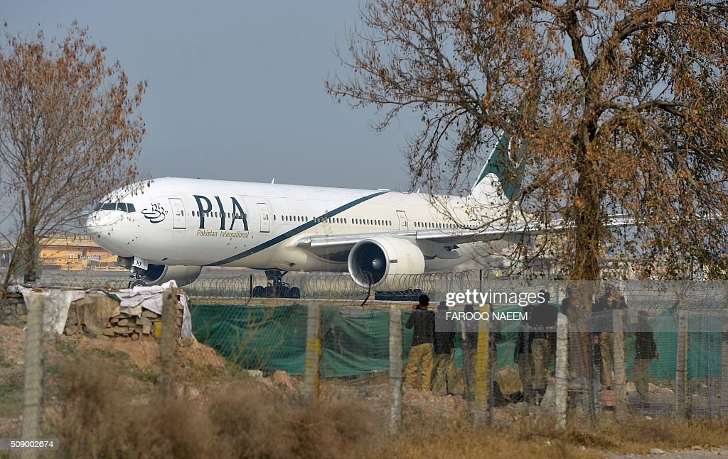 Pakistan policemen stand guard as a Pakistan International Airline (PIA) plane taxis on the runway on the way to Saudi Arabia during the PIA employees strike in Islamabad on February 8, 2016. The strike continued despite Prime Minister Nawaz Sharif's warning that the demonstration was illegal and those taking part could face up to a year in prison under a law that restricts union activity in state-administered sectors. AFP PHOTO / Farooq NAEEM / AFP / FAROOQ NAEEM