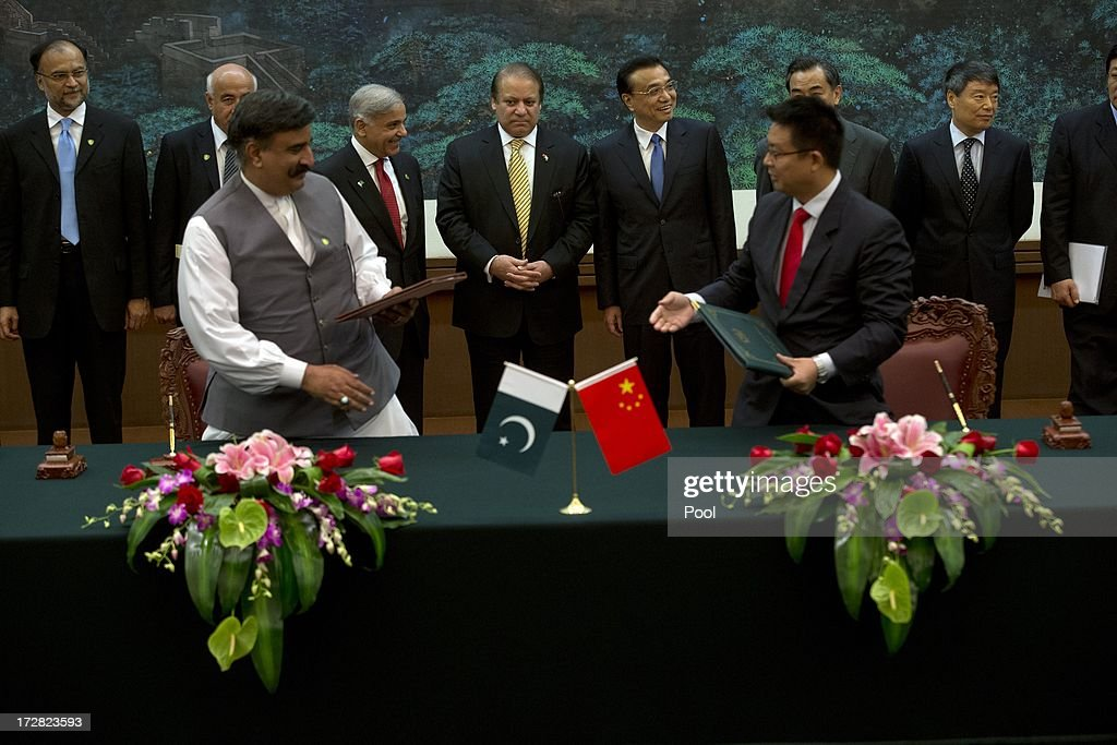 Pakistan Prime Minister Nawaz Sharif (C-L) and Chinese Premier Li Keqiang (C-R) observe a signing ceremony between officials from both countries held at the Great Hall of the People on July 5, 2013 in Beijing, China, Friday. This is Sharif's first foreign visit since returning to power and he is in China to negotiate investment to help his country's own failing economy, however trade between the two countries reached an all time high last year when it exceeded 12 billion USD.