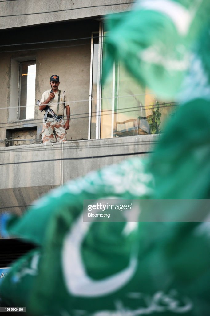 A Pakistan Ranger stands guard on a building during a demonstration in Karachi, Pakistan in Karachi, Pakistan, on Monday, May 13, 2013. Nawaz Sharif was headed for a record third term as prime minister of Pakistan as unofficial results from a landmark election gave him the convincing win he sought to tackle a slumping economy and growing militancy. Photographer: Asim Hafeez/Bloomberg via Getty Images