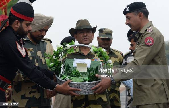 Pakistan Rangers Lieutenant Colonel Ashar Khan presents sweets to Indian Border Security Force Deputy Battalion Commander SD Negi at the...