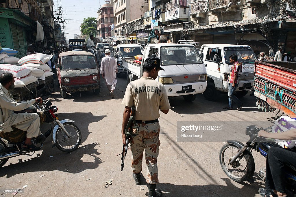 A Pakistan Rangers soldier armed with a weapon walks through a street at a wholesale market in Karachi, Pakistan, on Wednesday, May 8, 2013. Pakistan is to hold parliamentary elections on May 11. According to opinion polls, Nawaz Sharif of the Pakistan Muslim League-N (PMLN) leads Imran Khan of Pakistan Tehrik-e-Insaf (PTI) in the race to replace president Asif Ali Zadari and become Pakistan's 12th president. Photographer: Asim Hafeez/Bloomberg via Getty Images