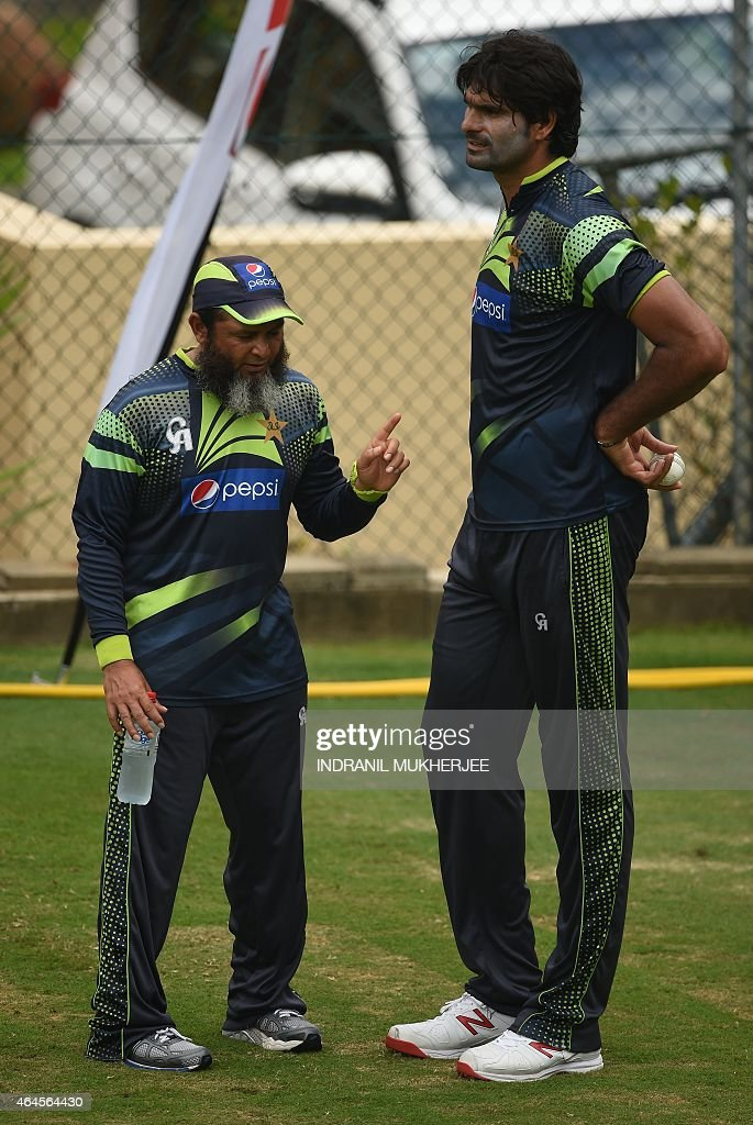 Pakistan spin bowling coach Mushtaq Ahmed speaks to cricketer Mohammad Irfan during their training session ahead of the 2015 Cricket World Cup Pool B...