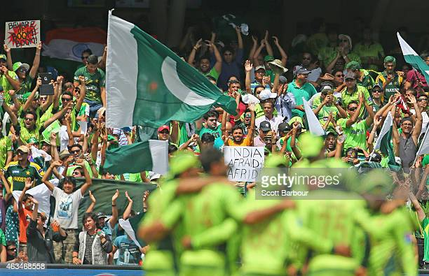 Pakistan supporters wave their flags as they celebrate the first Indian wicket during the 2015 ICC Cricket World Cup match between India and Pakistan...