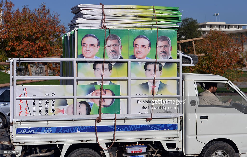A Pakistan worker drives a mini truck carrying banners featuring portraits of Egyptian President Mohamed Morsi, (top-R), Pakistani President Asif Ali Zardari (top-L) and Prime Minister Raja Pervez Ashraf along a street in Islamabad on March 17, 2013. Morsi will visit Pakistan this week on a one-day state visit, Pakistan's Foreign Ministry said. Morsi is due in the country on March 18 by invitation of President Asif Ali Zardari and will bring with him 'a high-powered delegation', according to a ministry spokesman.