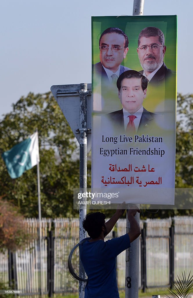 A Pakistan worker hangs a banner featuring portraits of Egyptian President Mohamed Morsi, (top-R), Pakistani President Asif Ali Zardari (top-L) and Prime Minister Raja Pervez Ashraf along a street in Islamabad on March 17, 2013. Morsi will visit Pakistan this week on a one-day state visit, Pakistan's Foreign Ministry said. Morsi is due in the country on March 18 by invitation of President Asif Ali Zardari and will bring with him 'a high-powered delegation', according to a ministry spokesman.