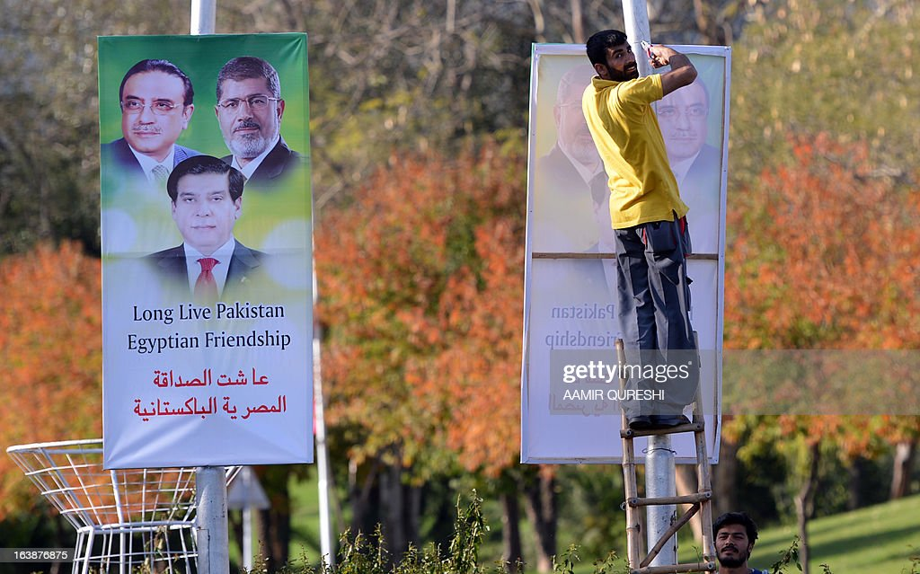 A Pakistan worker hangs banners featuring portraits of Egyptian President Mohamed Morsi, (top-R), Pakistani President Asif Ali Zardari (top-L) and Prime Minister Raja Pervez Ashraf along a street in Islamabad on March 17, 2013. Morsi will visit Pakistan this week on a one-day state visit, Pakistan's Foreign Ministry said. Morsi is due in the country on March 18 by invitation of President Asif Ali Zardari and will bring with him 'a high-powered delegation', according to a ministry spokesman.