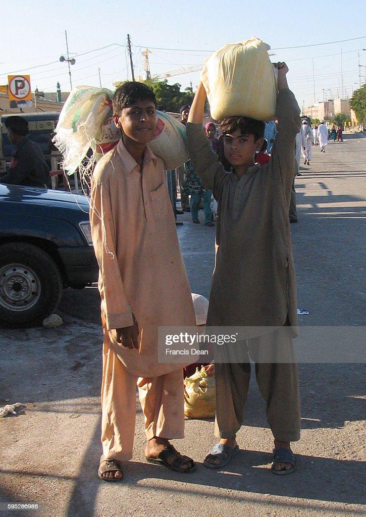 PAKISTAN_KARACHI_children boy carying goods and passing front of abdullah shah ghazi mazar at clifton in karachion nov2011{ PHOTO BY ILAS JDEAN/PAK...