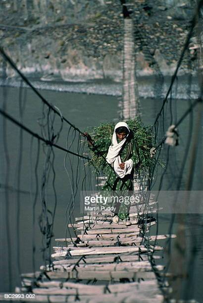 Pakistan,Hunza Valley,girl carrying animal fodder across footbridge