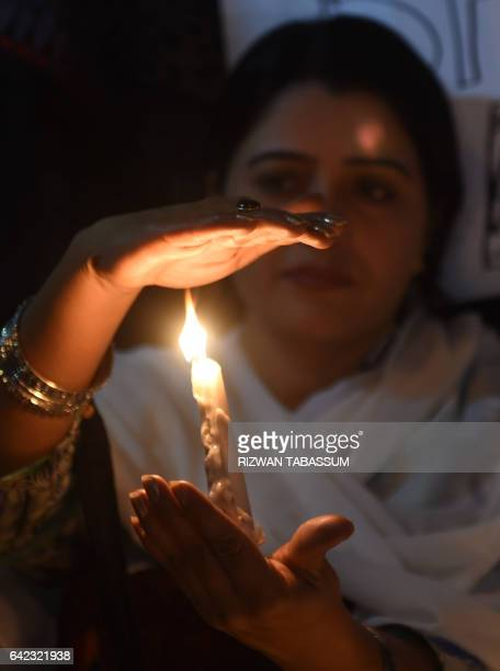 Pakistani activists and mourners light candles during a vigil in Karachi on February 17 to pay tribute to the victims of a bomb attack on the shrine...