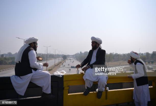 Pakistani activists from the TehreekiLabaik Yah Rasool Allah Pakistan religious group eat as they sit on a blocked flyover during a protest in...