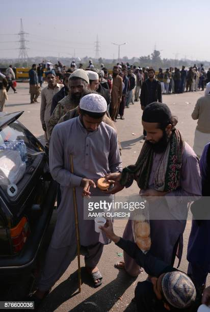 Pakistani activists from the TehreekiLabaik Yah Rasool Allah Pakistan religious group queue to receive food during a protest in Islamabad on November...