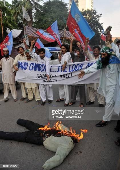 Pakistani activists of ShababeMilli a youth wing of hardline Islamic party JamateIslami shout slogans beside a burning effigy of British Prime...