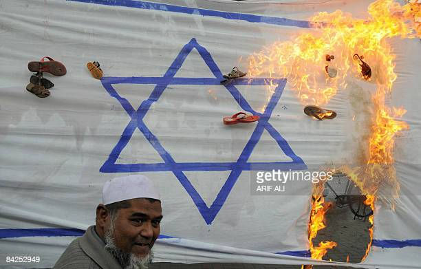 Pakistani activists of the banned JamaatudDawa and the fundamentalist JamaatiIslami party torch an Israeli flag during a protest in Lahore on January...