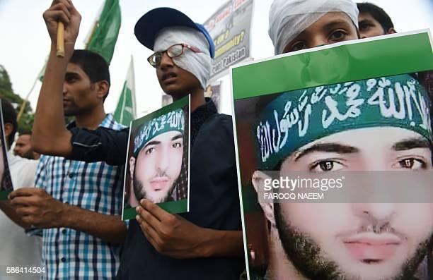 Pakistani activists of the hardline organisation JamaatudDawa carry posters bearing the image of slain Indian Kashmiri Hizbul Mujahideen commander...