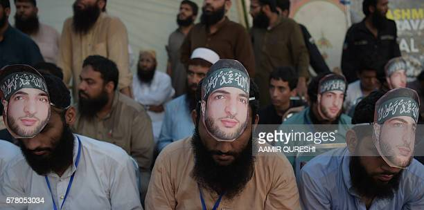 Pakistani activists of the hardline organisation JamaatudDawa wear masks of slain popular Indian Kashmiri rebel leader Burhan Wani at a rally to show...