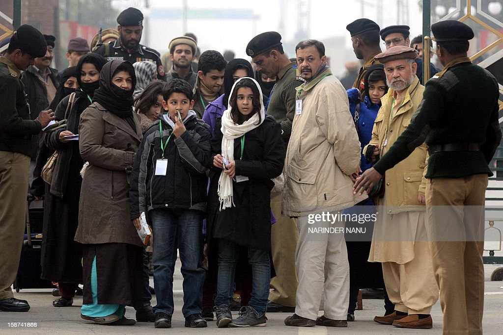 Pakistani Ahmadiyya Muslims wait as their documents are checked by officials at The India-Pakistan Wagah Border Post on December 27, 2012. Thousands of Ahmadiyya Muslims from across the world are scheduled to participate in the three day 121st Annual Convention of Ahmadiyya Muslim Jamat which is set to begin on December 29, at the organisation's international headquarters in Qadian.