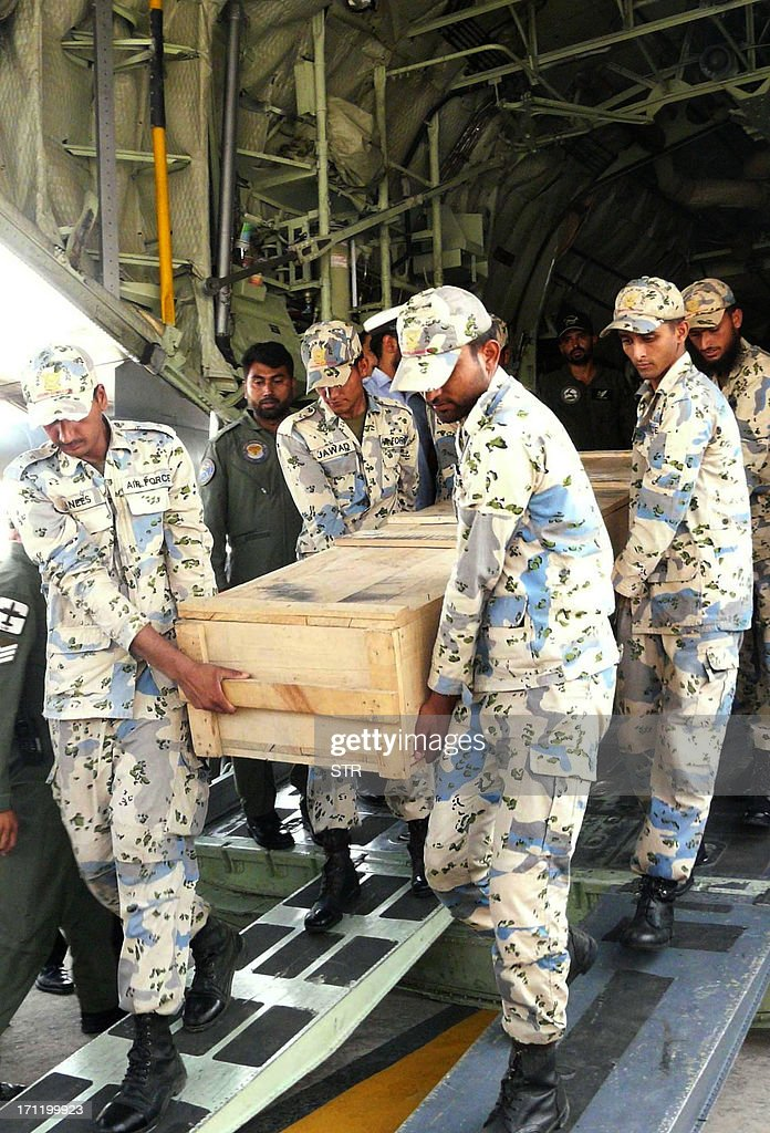 Pakistani air force personnel carry coffins of foreign tourists as they are unloaded from a C-130 air plane upon arrival at Chaklala airbase in Rawalpindi on June 23, 2013. Gunmen dressed as police killed nine Chinese and Ukrainian tourists in an unprecedented attack in the Pakistani Himalayas claimed by the Taliban, who said they had set up a new faction to target foreigners in revenge for US drone strikes. AFP PHOTO/STR
