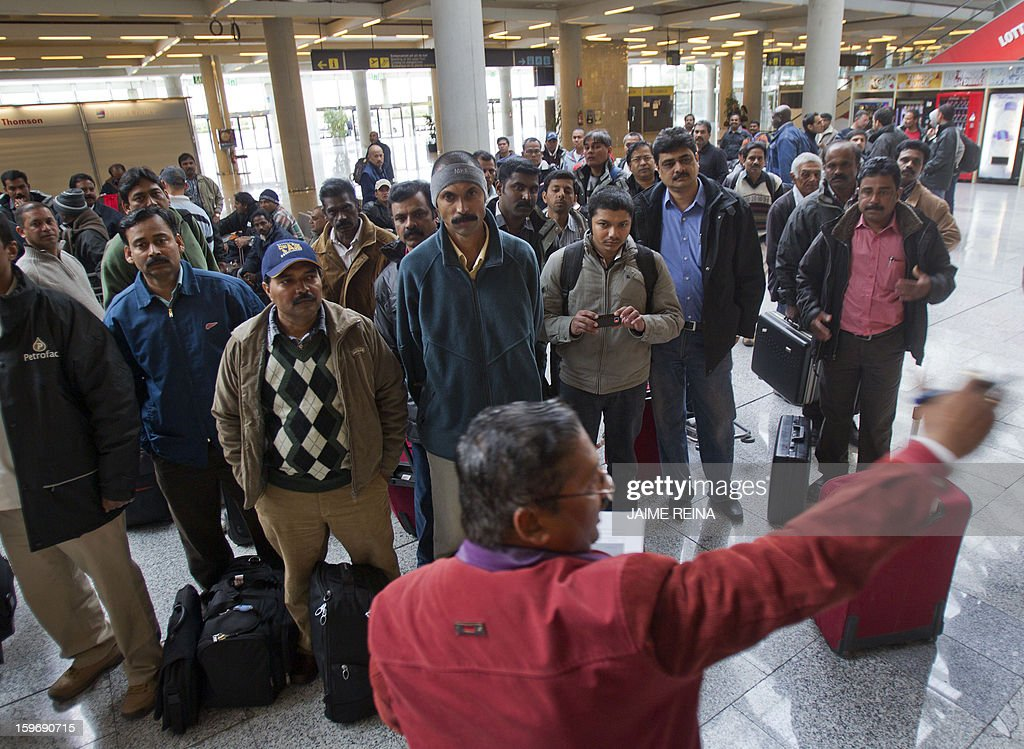 Pakistani and Indian employees of subcontracters working for British oil giant BP in Algeria listen to a man giving informations as they wait for their flight back to Dubai at the Palma de Mallorca airport on January 18, 2013. Foreign workers leave Algeria following an Algerian army rescue operation launched at the In Amenas plant on January 17, 2013 after kidnappers seized hostages at the site in what they said was retaliation for Algeria's support for French air strikes in Mali.